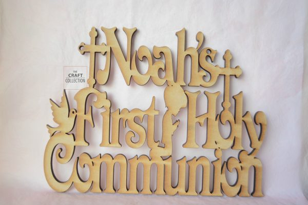 """Boy's First Holy Communion Sign, Personalised hanging signs laser cut Ireland. The Craft Collection providing craft shapes in Ireland. Features a light brown mdf laser cut sign that reads """"Noah's First Holy Communion"""" surrounded by a boy kneeling and praying a dove and a chalice against a dark grey background."""