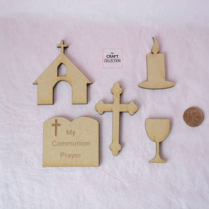 "First Holy Communion Craft Shapes Packet shows a pink background and 5 wodden shapes aid out beside a 1 cent coin. Shapes consist of small church, lighting candle, chalice, fancy cross and a bible engraved with a cross and ""My Communion Prayer"" by craft shapes supplier in Ireland The Craft Collection"