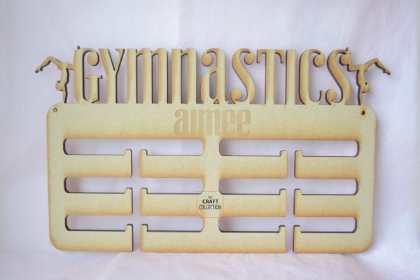 """Personalised Gymnastics Medal Holder, laser cut mdf medal holder craft blanks brown in colour against a pink background. It reads """"Gymnastics Aimee"""" and has two girls in Gymnastic poses at either side. By laser craft shapes supplier Ireland The Craft Collection"""