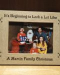 """A Family Christmas Photo Frame is a brown wooden picture frame on a brown mantle that reads """"It's beginning to look a lot like a Martin Christmas"""". A personalised family photo frame by Irish company The Craft Collection"""