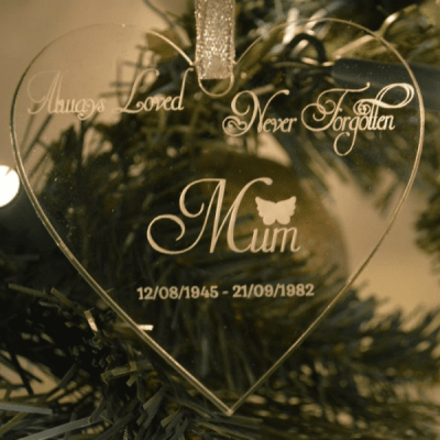 "Always Loved Never Forgotten Christmas Ornament . Shows a clear acrylic glass like heart hanging from a silver glittery ribbon with the words ""Always Loved Never Forgotten Mum 12.08.1945 - 21.09.1982"" in white writing and a picture of a white angel wings over the word Mum"