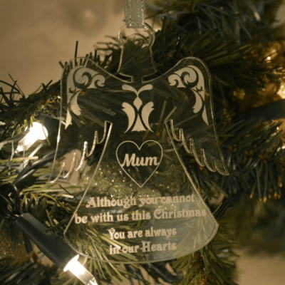 "Christmas Angel Tree Ornament clear glass like acrylic christmas tree ornament in the shape of an angel. Engraved with a heart and the word Mum inside the heart. Underneath the words ""Although you cannot be with us this Christmas you are always in our hearts"""