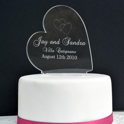 "Clear Acrylic Heart Cake Topper shows a black background and a white iced cake with a pink ribbon wrapped around the bottom. On top of the cake stands a glass like sideways heart engraved with two intertwined hearts and the words ""Jay and Sandra Villa Catignano August 12th, 2010"". Engraved personalised cake topper by The Craft Collection in Ireland"