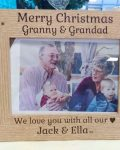 """A brown wooden photo frame against a light background that holds a photo of a grand father and mother holding two young children on their laps. It reads """"Merry Christmas Granny & Grandad, We love you with all our hearts Jack & Ella"""" (Where the word hearts is substituted with a heart emoji). From Irish company The Craft Collection"""