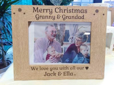 "A brown wooden photo frame against a light background that holds a photo of a grand father and mother holding two young children on their laps. It reads ""Merry Christmas Granny & Grandad, We love you with all our hearts Jack & Ella"" (Where the word hearts is substituted with a heart emoji). From Irish company The Craft Collection"