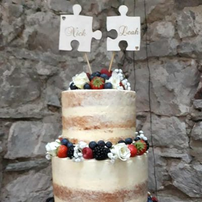 Jigsaw Cake Topper shows two puzzle pieces laser cut from birch plywood, Engraved with the names Nick and Leah and standing on top of a naked style wedding cake decorated with butter icing and fresh fruit against a natural stone background. This rustic cake topper was laser engraved by The Craft Collection in Ireland