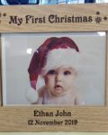 """My First Christmas Photo Frame is a brown wooden photo frame that is engraved with the words """"My First Christmas"""" and decorated with snowflakes at the top. On the bottom it can be personalised with baby's name and date of birth. From Irish company The Craft Collection"""