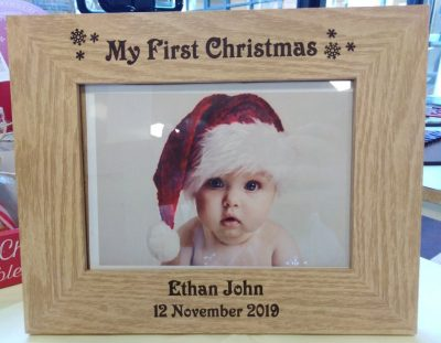 "My First Christmas Photo Frame is a brown wooden photo frame that is engraved with the words ""My First Christmas"" and decorated with snowflakes at the top. On the bottom it can be personalised with baby's name and date of birth. From Irish company The Craft Collection"