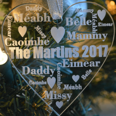 Our Family Christmas Tree Ornament features a clear acrylic glass-like heart ornament, see through with family names engraved or etched appearing in white writing. Hanging from a silver glittery ribbon with a Christmas tree and lights in the background.