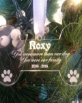 """Personalised Dog Memorial Ornament, picture of a clear acrylic, glass like, dog bone christmas tree ornament,hanging on a silver ribbon against a lit christmas tree background that reads """"Roxy, You were more the our dog, you were our family 2005-2018"""" by The Craft Collection Ireland"""