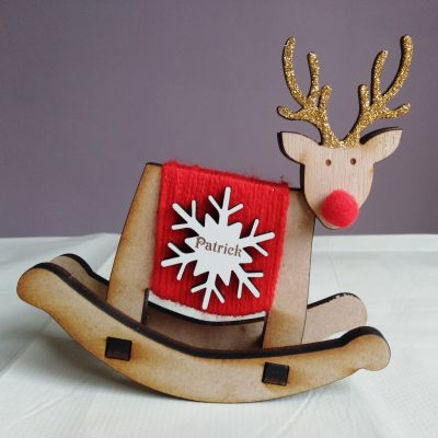 "Rockin' Reindeer is a free-standing rocking brown wooden reindeer. Body wrapped in red wool, with a red pom pom nose and gold glittered antlers. It has a personalised white snowflake badge on its body with the name ""Patrick"" laser engraved in brown."