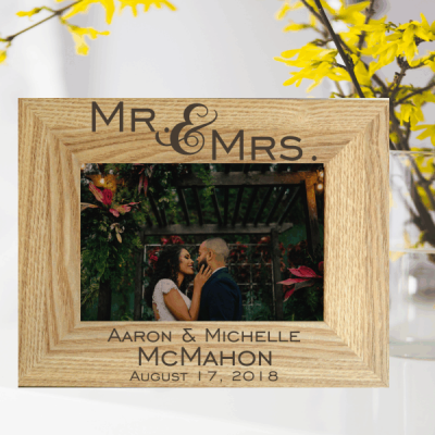 "Wedding Couple Photo Frame shows a light brown wooden photo frame standing in front of yellow flowers. It shoes a photo of a man and woman couple in a loving embrace and reads ""Mr & Mrs Aaron & Michelle McMahon August 17, 2018"" laser engraved personalised wedding gifts by The Craft Collection Ireland"
